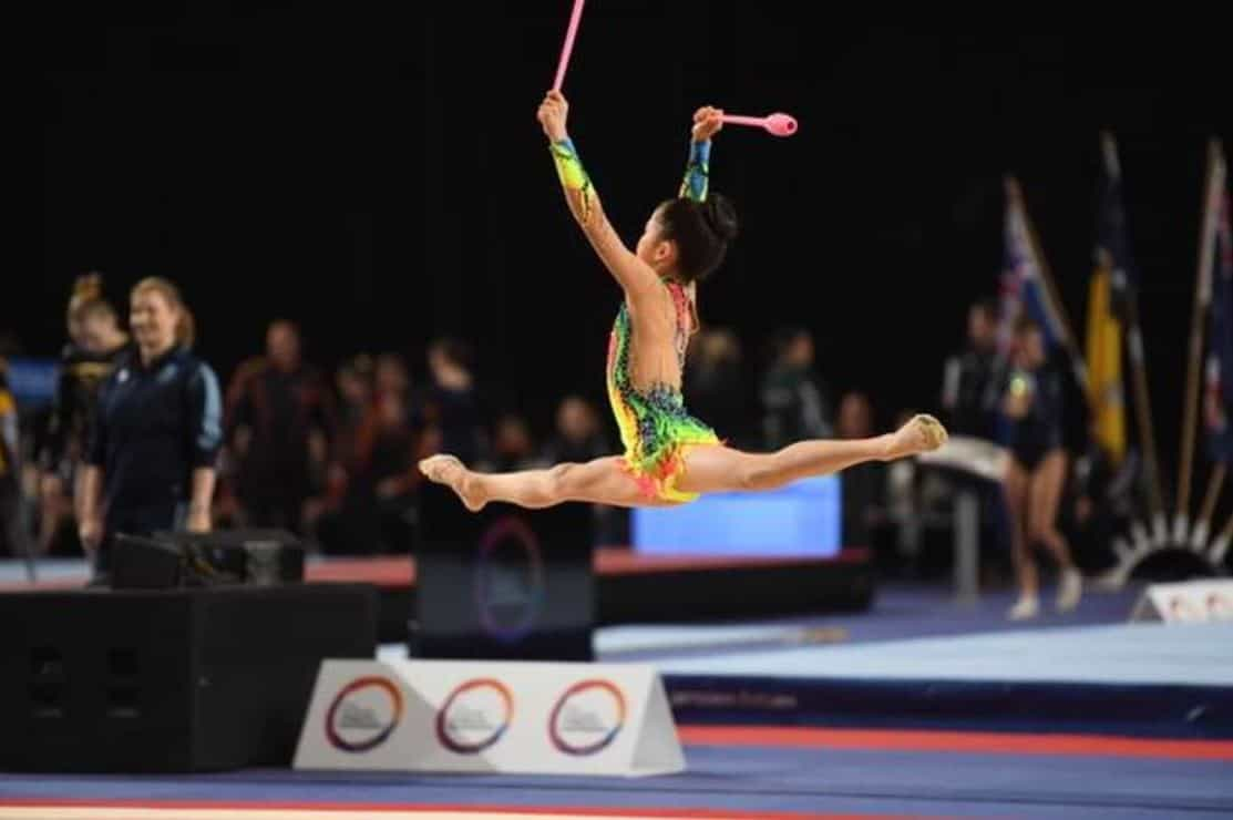 gymnastics competiotion girl in air with wands