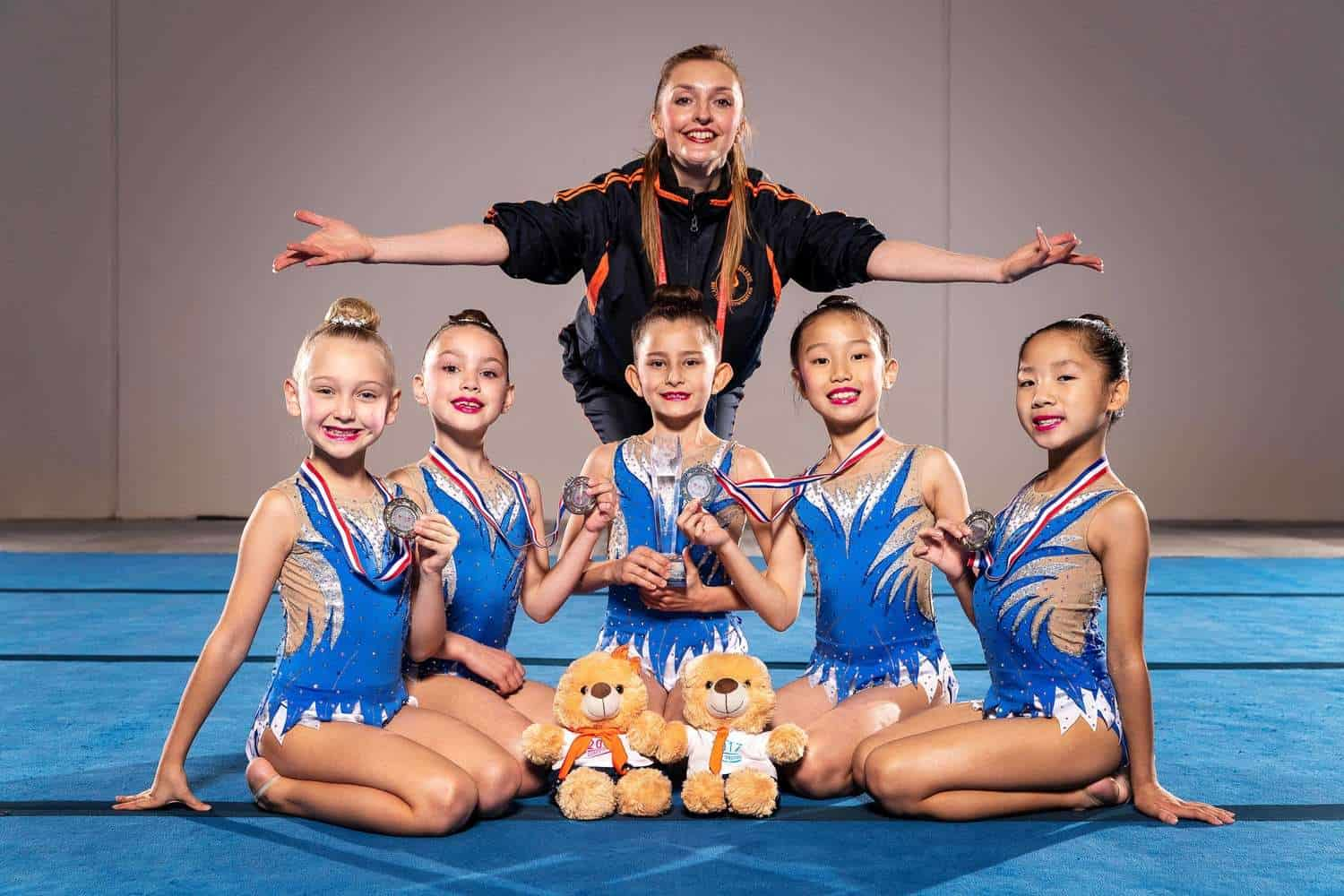 aesthetic group gymnastics five girls and trainer